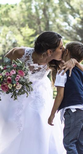 une mariée avec un bouquet de fleurs embrasse son enfant