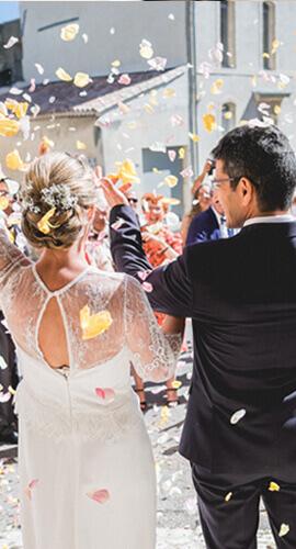 deux mariés reçoivent des pétales de rose